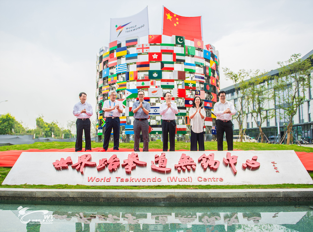 Dr. Choue (second from the left) is taking a photo in front of sculpture with 209 flags which represent each of the WT Member National Associations