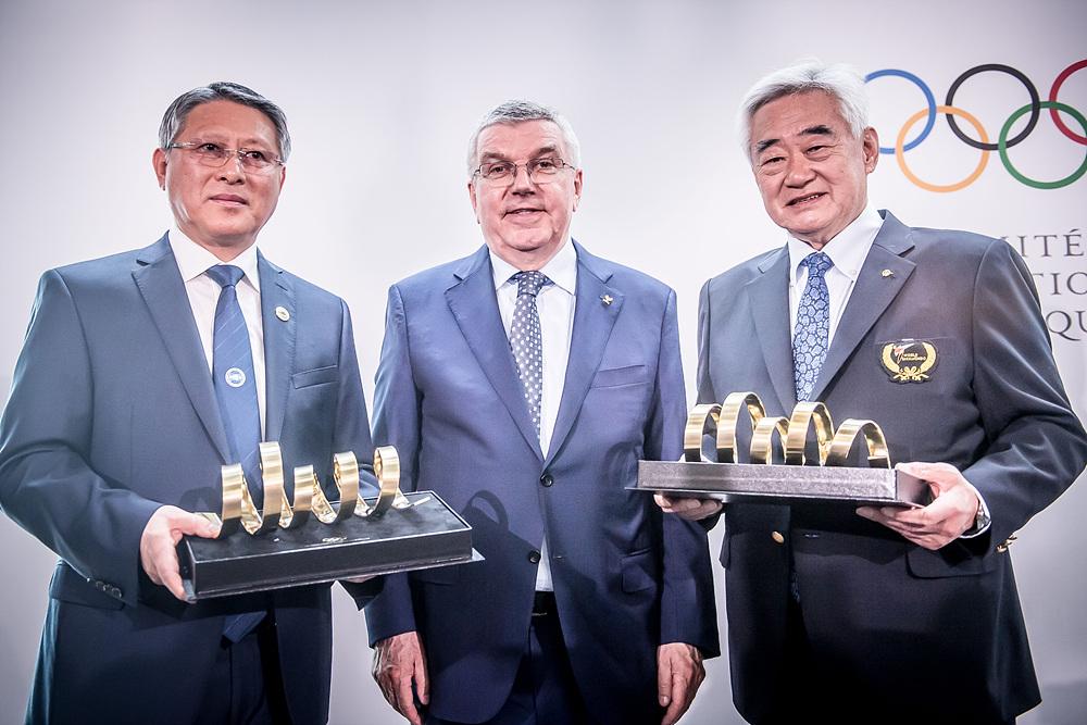 ITF 리용선 총재(왼쪽)와 WT 조정원 총재(오른쪽)가 IOC 토마스 바흐 위원장(가운데)이 준비한 올림픽 트로피 기념품을 들고 기념사진 촬영을 하고있다.